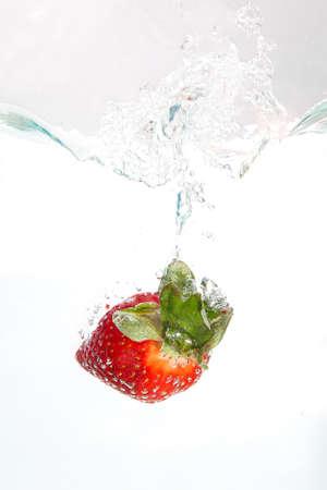 Strawberri splashing into water on white