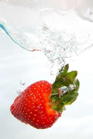 Fresh red strawberri splashing into water on white Stock Photo