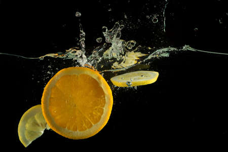Fruits orange and  lemon slices splash in water on black background