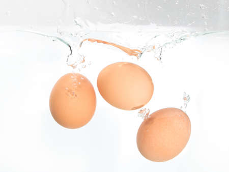 Three eggs splash with water on the white