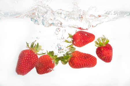 Strawberries splashing in to water on the white background