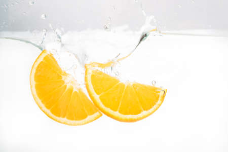 Two lemon slices splash in water on white background Stock Photo