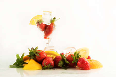 Cocktail, fruits and ice on white background