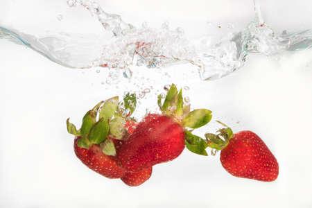 Strawberries splashing in to water on the white Stock Photo