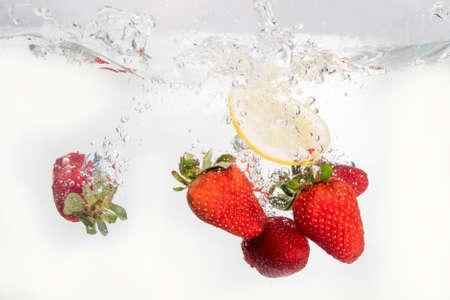 Strawberries and lemon slice splashing in to water on the white Stock Photo