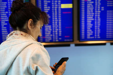 Woman with mobile phone is looking for a flight schedule on timetable