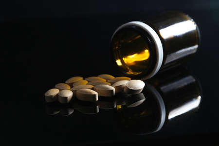 Glass bottle and bunch of painkiller pills on black Banco de Imagens
