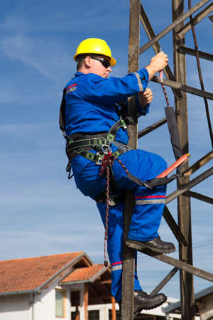 Electrician with safety belt working on electric power pole