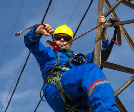 Technician prepares safety belt to work on lamppost