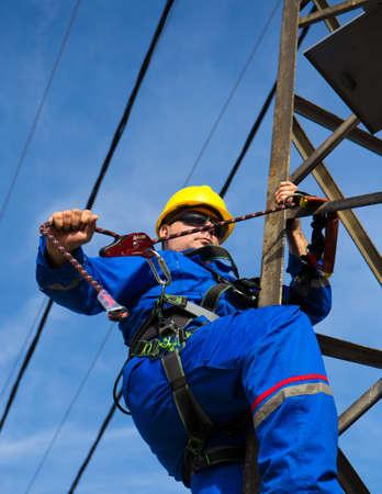 Electrician prepares safety belt to work on lamppost Reklamní fotografie