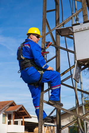 Electrician with safety belt working on electric lamppost