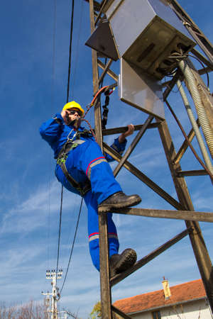 Electrician taking photos on the electric power pole with cell phone