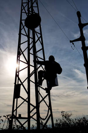 Silhouette of a worker climbing on the electric pole