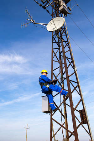 Electrician with yellow helmet and laptop on the lamppost