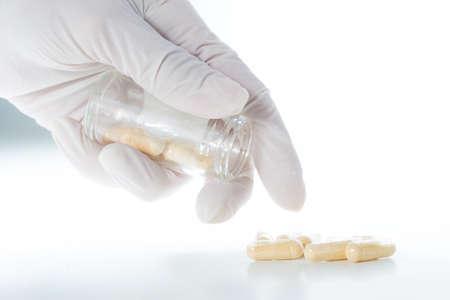 Man in white gloves takes transparent probiotics capsule 写真素材