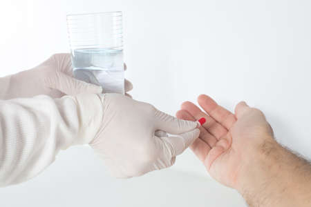 The paramedic administers the antibiotic capsule and glass of water to the patient 写真素材