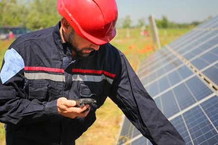 Worker in a red helmet controls the solar panel