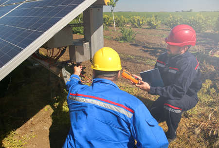 Two electricians are controling  solar panel Фото со стока