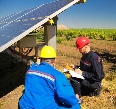 Two electricians are repair solar panel Фото со стока
