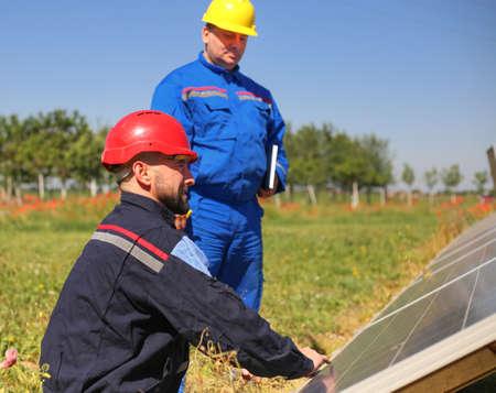 Green energy, two technicians control solar panels Фото со стока