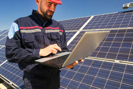 Tehnician in a red helmet and laptop in the solar power plant