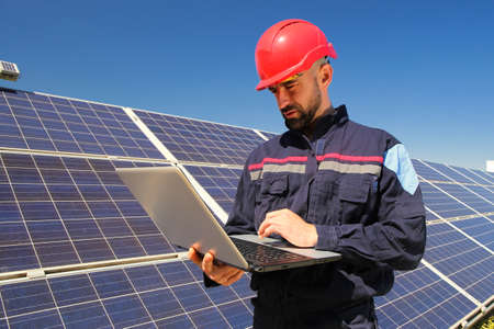 Electrician in a red helmet and laptop in the solar power plant