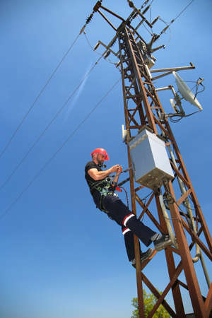 Electrician in red helmet working on power transmission line Stock Photo