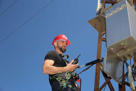 Tehnician in red helmet and safety belt with radio station on the electric pole