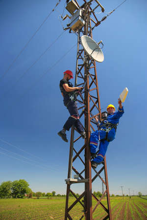 Two electricians install 4G telecommunications antenna system Stock Photo