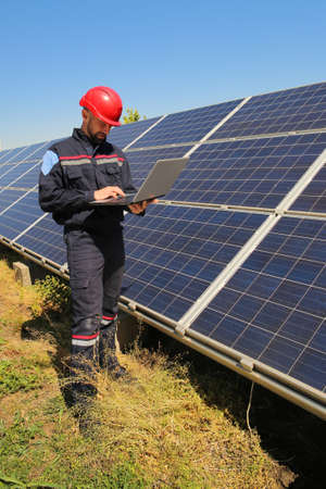 Tehnician in a red helmet with laptop and the solar panels Stock Photo