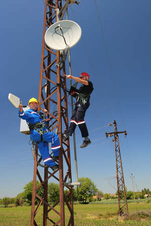 Two electricians install telecommunications antenna system