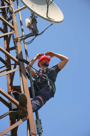 Worker in red helmet working on 5G antenna system Stock Photo