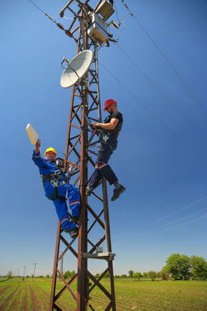 Two tehnicians install telecommunications antenna system