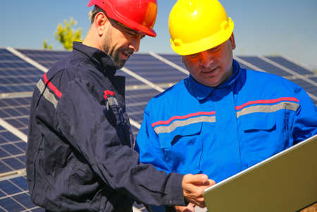 Green energy, power plant and two tehnicians with laptop Stock Photo