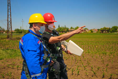 Two workers with masks control the 4G antenna in Covid-19 pandemic  Stock Photo
