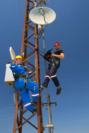 Two workers in protective workwear install telecommunications antenna system