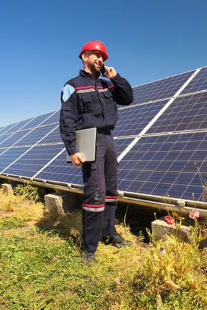 Eletrician in a red helmet makes a phone call in the solar power plant
