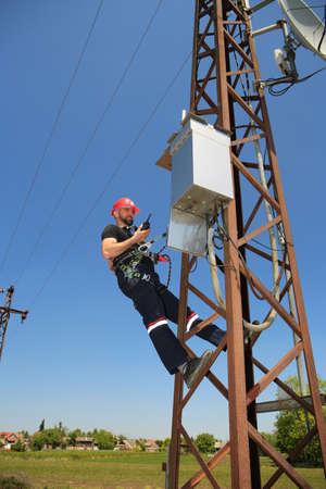 Tehnician in red helmet make radio call on power transmission line Stock Photo