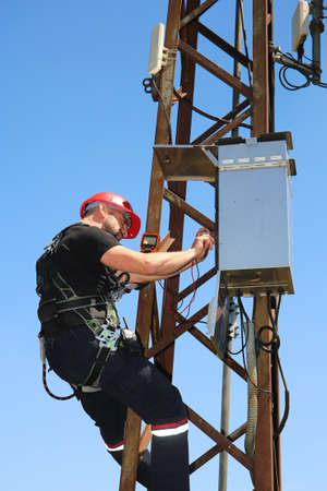 Tehnician in red helmet with multimeter on the electric pole