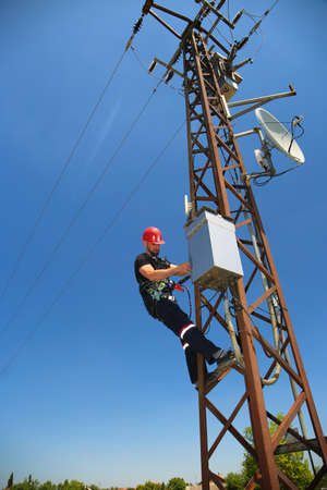 Electrician in red helmet working on 5G antenna system