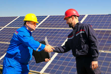 two elektricians shake hands in front of the solar power plant