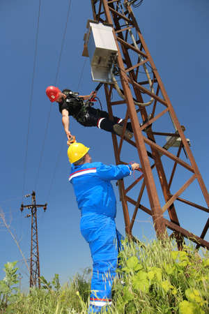 Two tehnicians are working on power transmission line Stock Photo