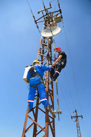Two tehnicians  with safety belt are working on power transmission line