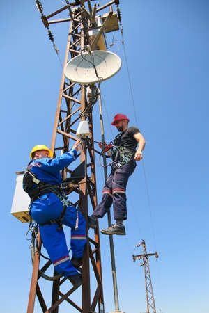 Two electricians with safety belt are working on power transmission line