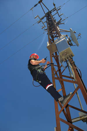 Tehnician in red helmet and safety belt make radio call on the electric pole