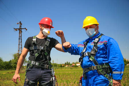 The two electricians greet each other after a successful job during the Covid 19 pandemic Stock Photo