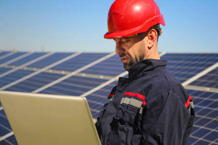Portrait of Electrician in a red helmet and laptop in the solar power plant, green energy Stock Photo