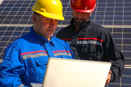 Green energy, two tehnicians with a laptop and solar panels