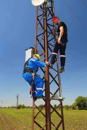 Two eletricians  with safety belt are working on power transmission line