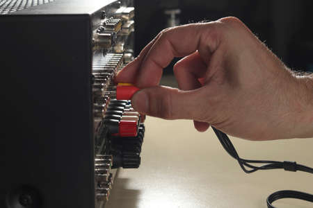 The Technician connects the audio cables to the rack